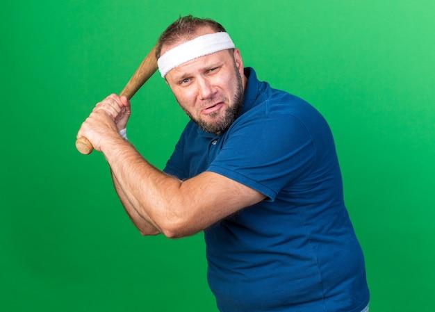 Ängstlicher erwachsener slawischer sportlicher mann, der stirnband und armbänder hält, die fledermaus lokalisiert auf grüner wand mit kopienraum halten
