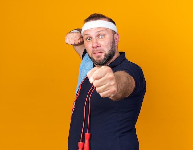 Ängstlicher erwachsener slawischer sportlicher mann mit springendem seil um hals und mit handtuch auf schulter tragendem stirnband und armbändern, die fäuste bereit halten, isoliert auf orange wand mit kopienraum zu schlagen