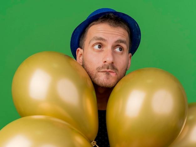Ängstlicher gutaussehender mann, der blauen parteihut trägt, hält heliumballons lokalisiert auf grüner wand mit kopienraum