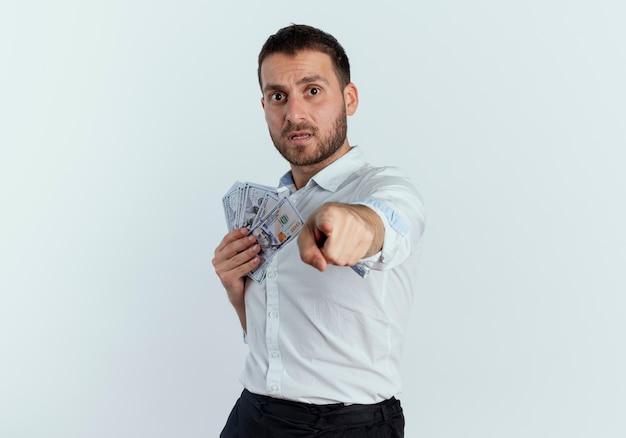 Ängstlicher gutaussehender mann hält geld und punkte isoliert auf weißer wand