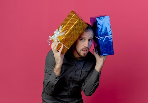 Ängstlicher gutaussehender mann versteckt kopf, der geschenkboxen lokalisiert auf rosa wand hält