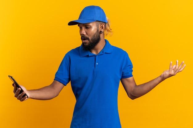 Ängstlicher junger afroamerikanischer lieferbote, der das telefon auf orangefarbenem hintergrund mit kopienraum hält und anschaut