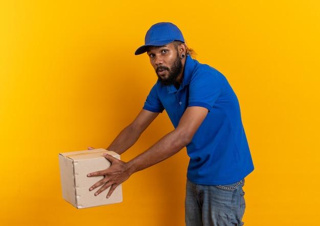 Ängstlicher junger afroamerikanischer lieferbote, der einen karton isoliert auf orangefarbenem hintergrund mit kopierraum hält