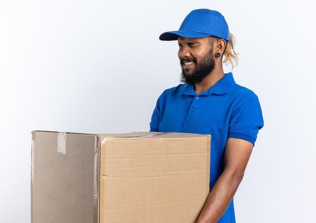 Ängstlicher junger afroamerikanischer lieferbote, der einen schweren karton isoliert auf weißem hintergrund mit kopienraum hält