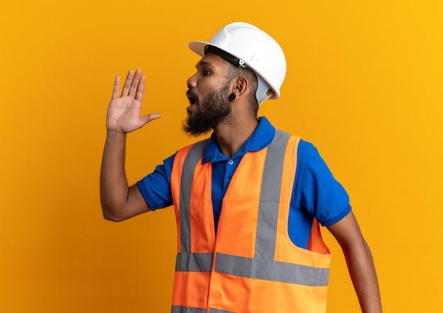 Ängstlicher junger baumeister in uniform mit schutzhelm, der jemanden anruft, der auf orangefarbener wand mit kopienraum isoliert auf die seite schaut