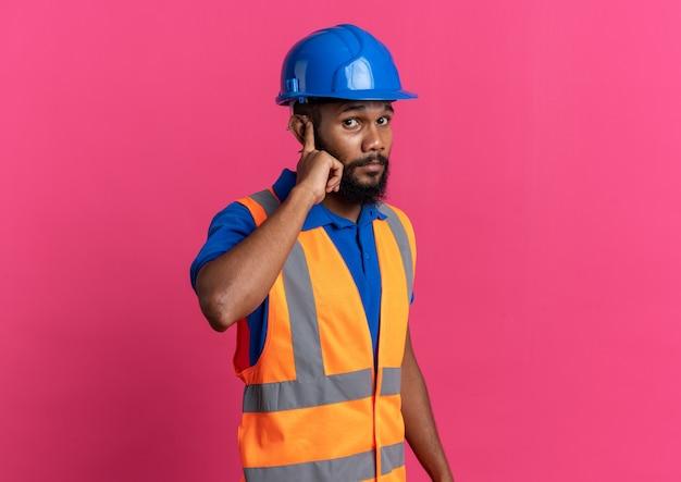 Ängstlicher junger baumeister in uniform mit schutzhelm, der seinen finger auf das ohr legt, isoliert auf rosa wand mit kopierraum