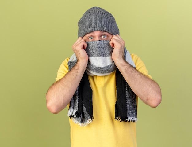Ängstlicher junger blonder kranker slawischer mann, der wintermütze trägt und gesicht bedeckt