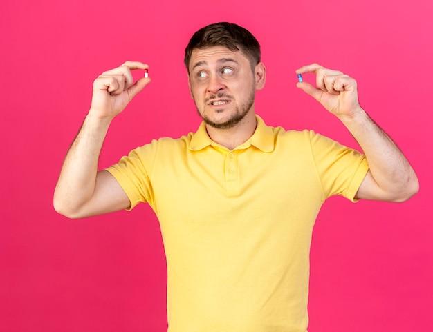 Ängstlicher junger blonder kranker slawischer mann hält und betrachtet medizinische kapseln auf rosa