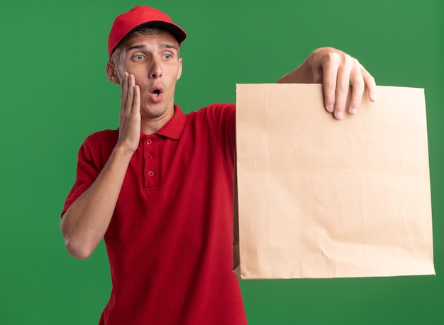 Ängstlicher junger blonder lieferjunge legt hand auf gesicht, das papierpaket auf grün hält und betrachtet