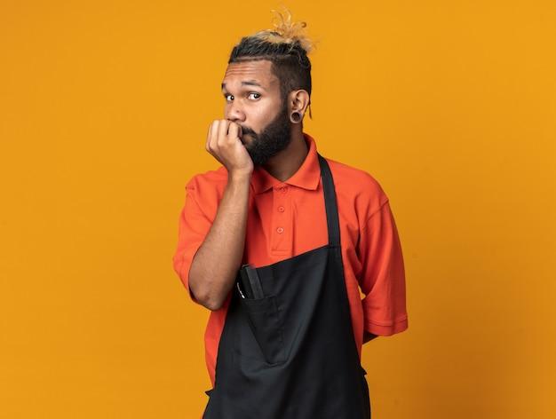 Ängstlicher junger friseur in uniform, der die hand hinter dem rücken und auf den lippen hält, die auf der vorderseite isoliert auf einer orangefarbenen wand mit kopienraum suchen
