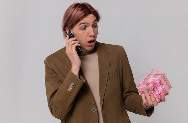 Ängstlicher junger gutaussehender mann, der am telefon spricht und geschenkbox betrachtet