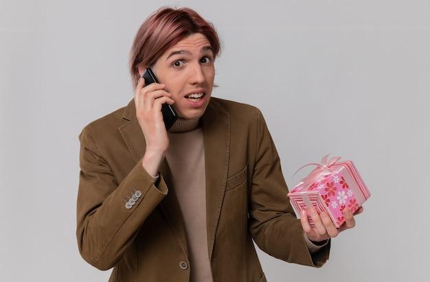 Ängstlicher junger gutaussehender mann, der am telefon spricht und geschenkbox hält