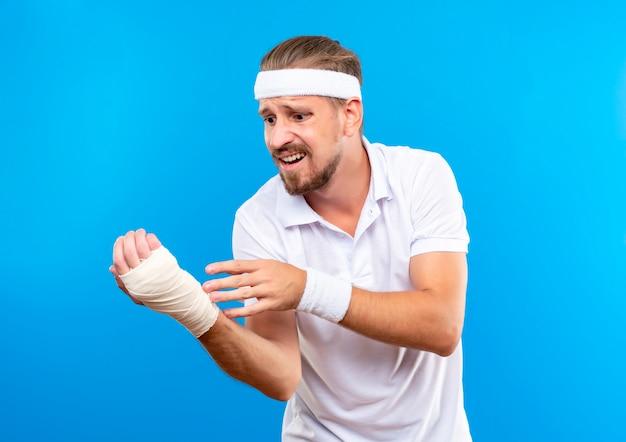 Ängstlicher junger, gutaussehender, sportlicher mann mit stirnband und armbändern, der sein verletztes handgelenk betrachtet, das mit verband isoliert auf blauer wand gewickelt ist