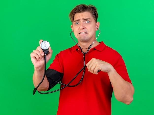 Ängstlicher junger hübscher blonder kranker mann, der stethoskop trägt, das druck zu sich selbst hält, der blutdruckmessgerät hält, das vorne lokalisiert auf grüner wand betrachtet