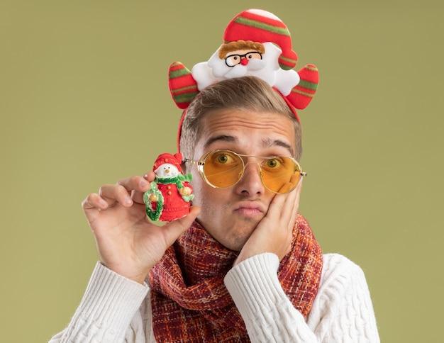 Ängstlicher junger hübscher kerl, der weihnachtsmann-stirnband und schal trägt, die kamera betrachten, die schneemann-weihnachtsverzierung hält, die hand auf gesicht lokalisiert auf olivgrünem hintergrund hält