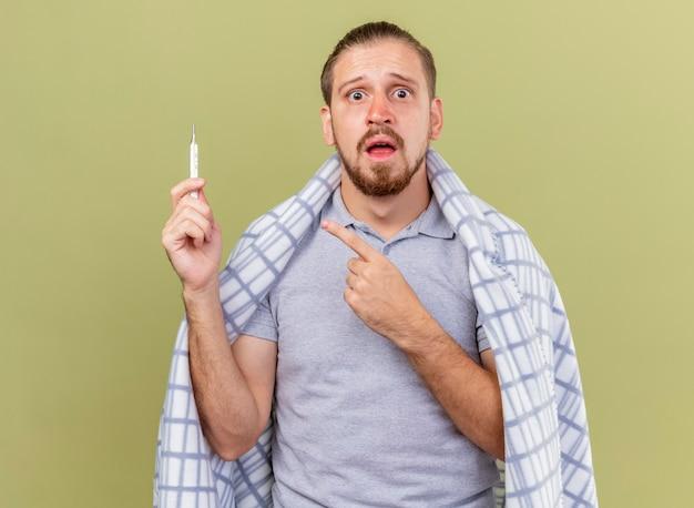 Ängstlicher junger hübscher kranker mann gewickelt in kariertem halten und zeigen auf thermometer, das front lokalisiert auf olivgrüner wand betrachtet