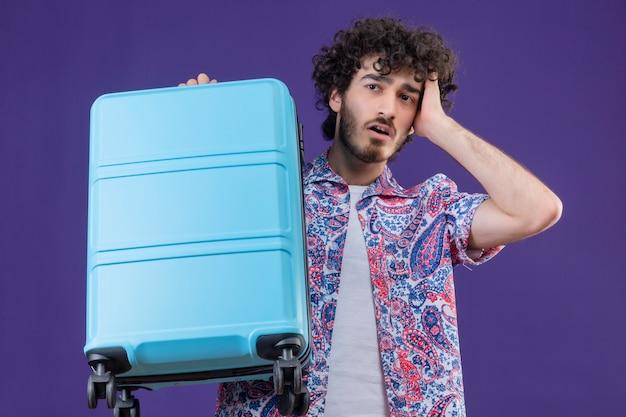Ängstlicher junger hübscher lockiger reisender mann, der koffer mit hand auf kopf auf lokalisiertem lila raum hält