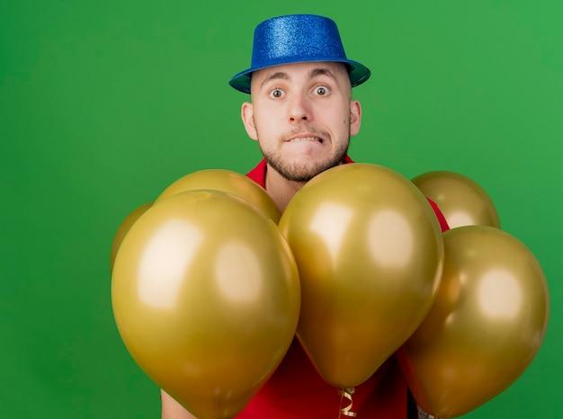Ängstlicher junger hübscher party-typ, der partyhut trägt, der unter luftballons steht und die vordere beißende lippe lokalisiert auf grüner wand betrachtet