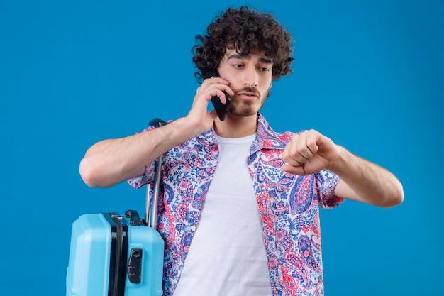 Ängstlicher junger hübscher reisender mann, der am telefon mit geballter faust spricht, die seine hand mit koffer auf isoliertem blauem raum betrachtet