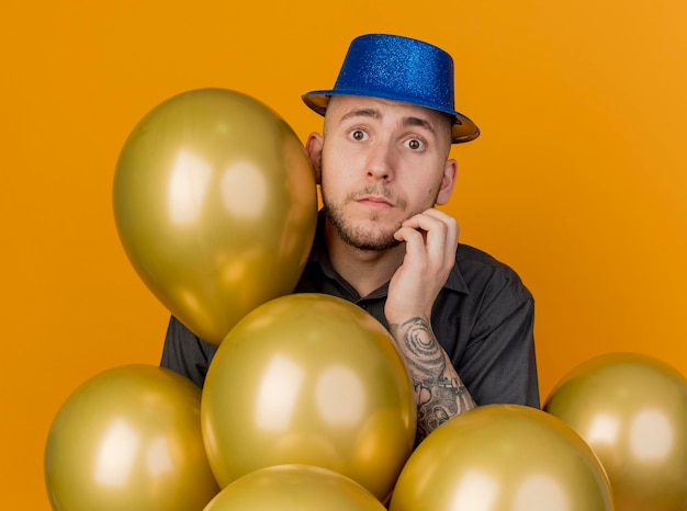 Ängstlicher junger hübscher slawischer party-typ, der partyhut trägt, der hinter luftballons steht, die das vordere berührende gesicht lokalisiert auf orange wand betrachten
