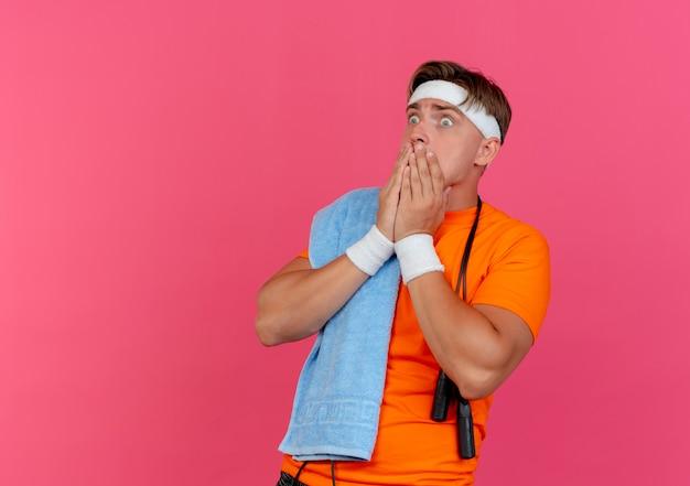 Ängstlicher junger hübscher sportlicher mann, der stirnband und armbänder mit handtuch und springseil um den hals trägt und gerade hände auf mund lokalisiert auf rosa mit kopienraum schaut