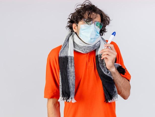 Ängstlicher junger kaukasischer kranker mann, der brille und maske hält thermometer lokalisiert auf weißer wand trägt