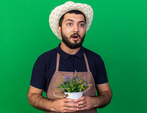 Ängstlicher junger kaukasischer männlicher gärtner, der einen gartenhut trägt, der blumentopf hält und die seite isoliert auf grüner wand mit kopienraum betrachtet