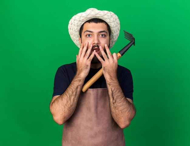 Ängstlicher junger kaukasischer männlicher gärtner mit gartenhut legt die hände auf den mund und hält rechen isoliert auf grüner wand mit kopierraum with