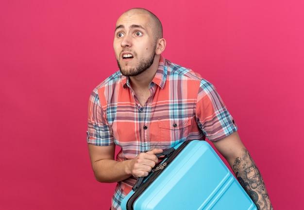 Ängstlicher junger kaukasischer reisender, der koffer hält und die seite einzeln auf rosafarbenem hintergrund mit kopienraum betrachtet