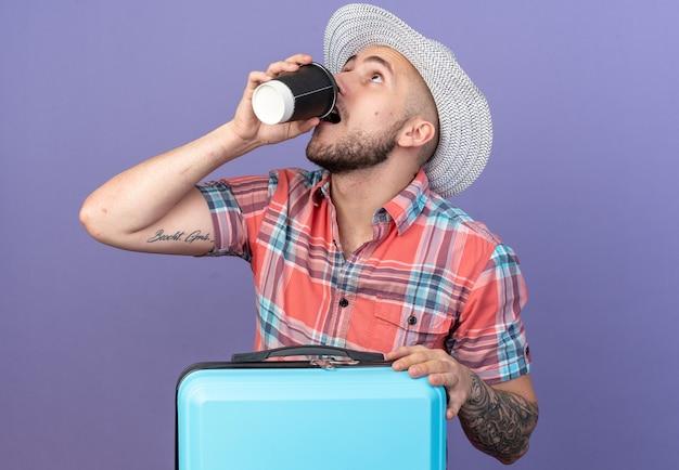 Ängstlicher junger kaukasischer reisender mit strohhut, der aus pappbecher trinkt, der hinter koffer steht, isoliert auf violettem hintergrund mit kopierraum