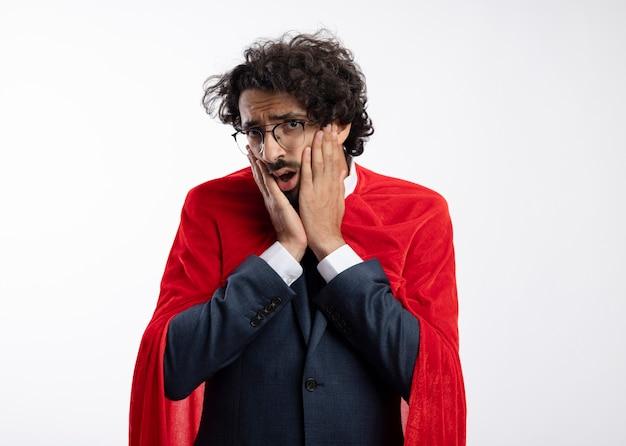 Ängstlicher junger kaukasischer superheldenmann in optischer brille, der anzug mit rotem mantel trägt, legt hände auf gesicht