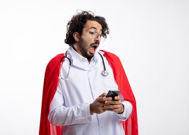 Ängstlicher junger kaukasischer superheldenmann in optischer brille, der eine arztuniform mit rotem mantel trägt und mit stethoskop um den hals hält und auf das telefon schaut