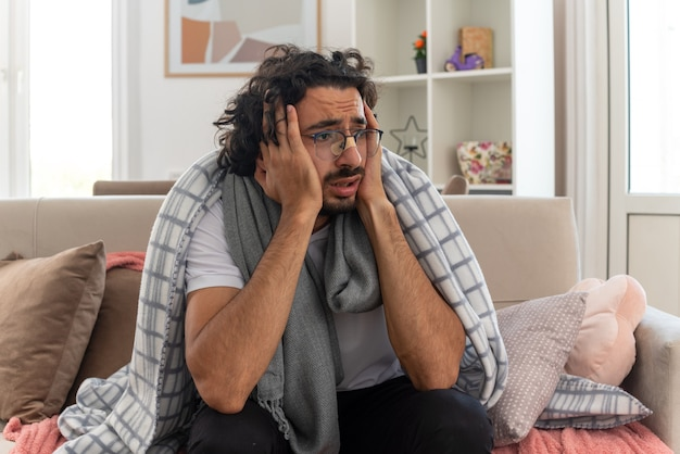 Ängstlicher junger kranker kaukasischer mann in optischer brille, eingewickelt in plaid mit schal um den hals, der die hände auf sein gesicht legt, der auf der couch im wohnzimmer sitzt