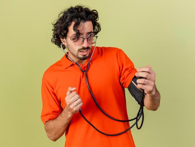 Ängstlicher junger kranker mann, der brille und stethoskop trägt, die seinen druck mit blutdruckmessgerät messen, das auf olivgrüner wand lokalisiert wird