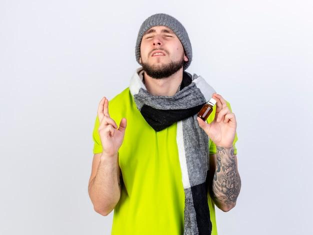 Ängstlicher junger kranker mann, der wintermütze und schal trägt, kreuzt finger und hält medizin in einer glasflasche, die auf weißer wand lokalisiert wird