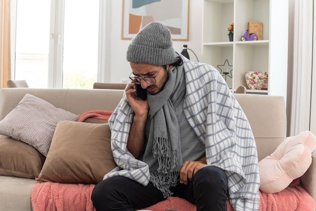Ängstlicher junger kranker mann in optischer brille, eingewickelt in plaid mit schal um den hals, der eine wintermütze trägt und am telefon spricht, sitzt auf der couch im wohnzimmer
