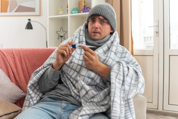 Ängstlicher junger kranker mann mit schal um den hals, der eine wintermütze trägt, die in plaid gewickelt ist und ein thermometer auf der couch im wohnzimmer hält