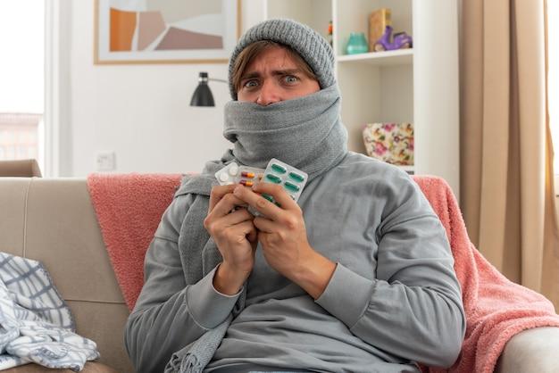Ängstlicher junger kranker slawischer mann, der seinen mund mit einem schal bedeckt, der eine wintermütze trägt und medizinblisterpackungen hält, die auf der couch im wohnzimmer sitzen?