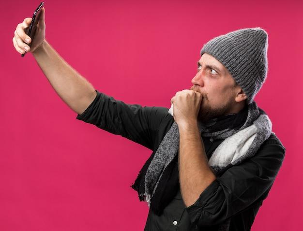 Ängstlicher junger kranker slawischer mann mit schal um den hals, der eine wintermütze trägt, hält die faust nahe am mund, hält und schaut auf das telefon