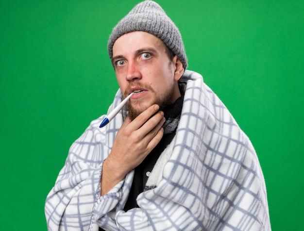 Ängstlicher junger kranker slawischer mann mit schal um den hals, der in karierten wintermützen gehüllt ist und ein thermometer im mund hält, isoliert auf grüner wand mit kopierraum
