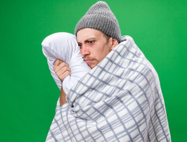 Ängstlicher junger kranker slawischer mann mit schal um den hals, der in plaid gehüllt ist und wintermütze trägt, hält kissen isoliert auf grüner wand mit kopierraum