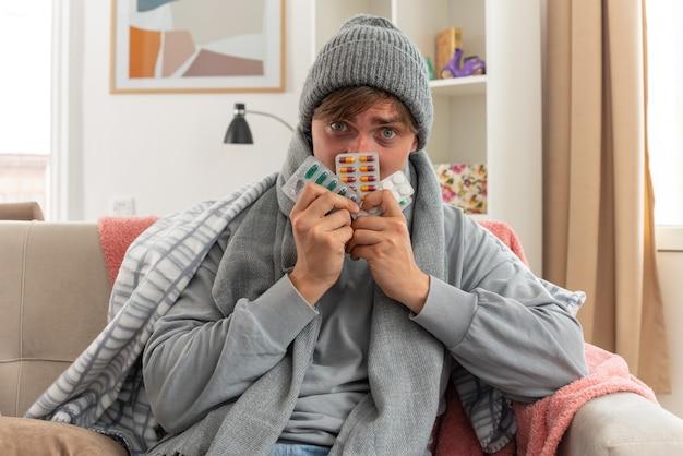 Ängstlicher junger kranker slawischer mann mit schal um den hals mit wintermütze, der medizinblisterpackungen auf der couch im wohnzimmer hält