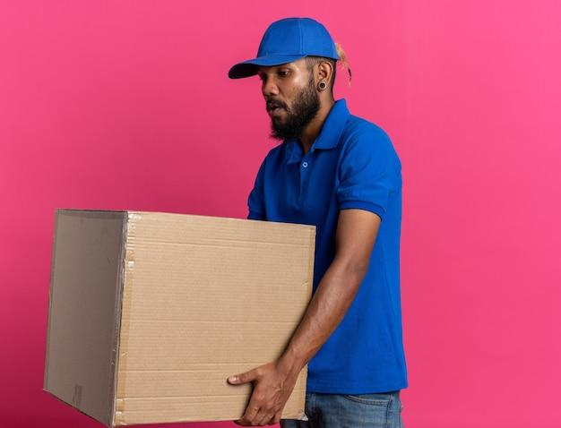 Ängstlicher junger lieferbote, der einen schweren karton isoliert auf rosa wand mit kopierraum hält