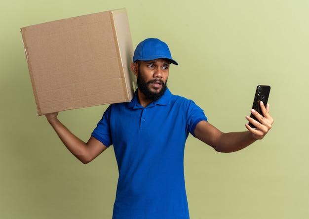 Ängstlicher junger lieferbote, der karton hält und telefon isoliert auf olivgrüner wand mit kopienraum betrachtet