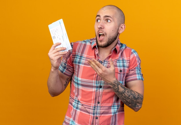 Ängstlicher junger reisender, der auf orangefarbener wand mit kopierraum isolierte flugtickets hält und zeigt