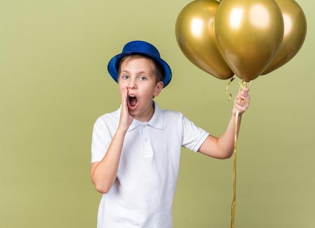 Ängstlicher junger slawischer junge mit blauem partyhut, der heliumballons hält und die hand nah am mund hält, und jemanden anruft, der auf olivgrüner wand mit kopienraum isoliert ist