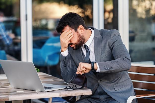 Ängstlicher kaukasischer bärtiger geschäftsmann, der im café sitzt, seinen kopf hält und nervös wird, weil er vergisst, sich mit einem wichtigen kunden zu treffen.