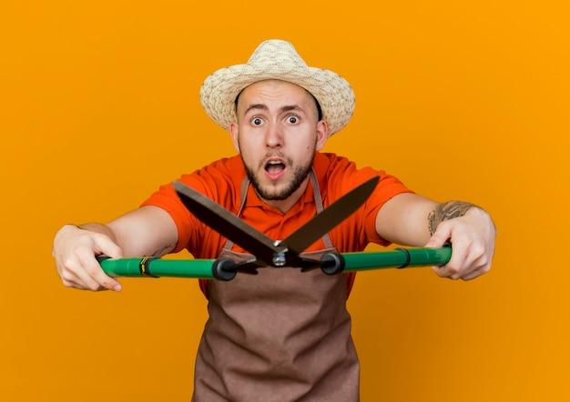 Ängstlicher männlicher gärtner, der gartenhut trägt, hält gartenschere