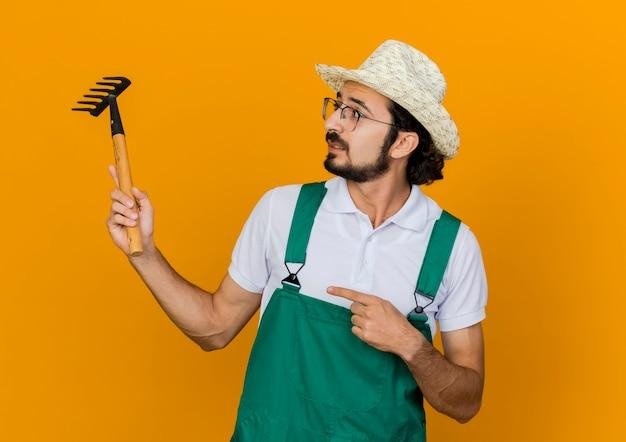 Ängstlicher männlicher gärtner in optischer brille, die gartenhutgriffe trägt und auf rechen zeigt