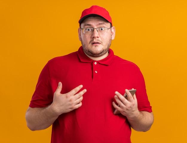 Ängstlicher übergewichtiger junger lieferbote in optischer brille, der das telefon isoliert an der orangefarbenen wand mit kopienraum hält